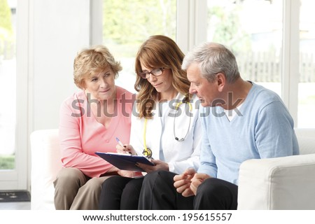 Beautiful female doctor analyzing x-ray with elderly patients. - stock photo