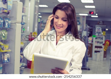 Beautiful female doctor working in pharmacy - stock photo
