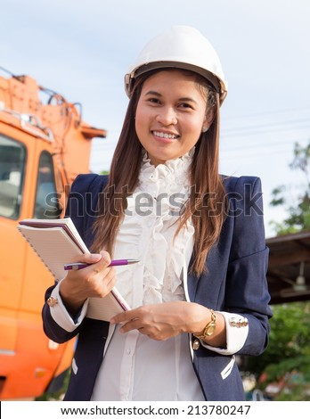 Beautiful female engineer wearing a helmet checking the list. - stock photo