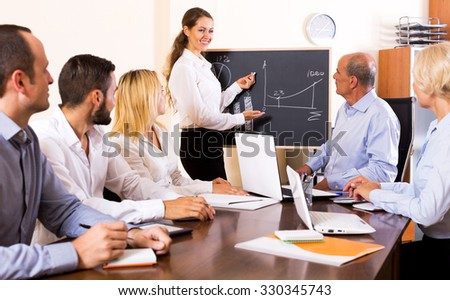 Beautiful female expert makes a presentation at a meeting in the office - stock photo