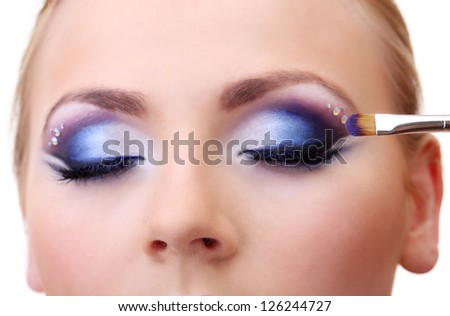 Beautiful female eyes with bright blue make-up and brush - stock photo