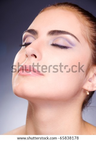 beautiful female face with make-up closed eyes on gray background - stock photo