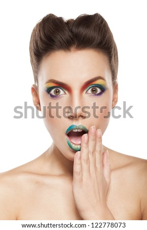 beautiful female face with rainbow makeup. bewildered girl touching her face by hand - stock photo