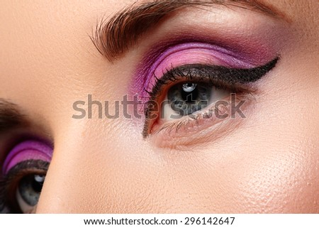 Beautiful female face with sexy black liner and bright purple makeup. - stock photo