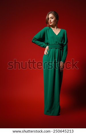 Beautiful female fashion model posing in green dress  her hand on hip. Isolated. Red background. - stock photo
