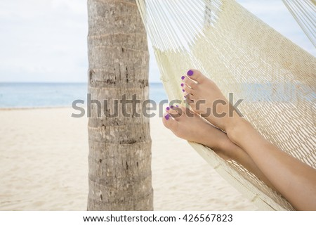 Beautiful female feet in a hammock on the beach at a tropical island resort - stock photo