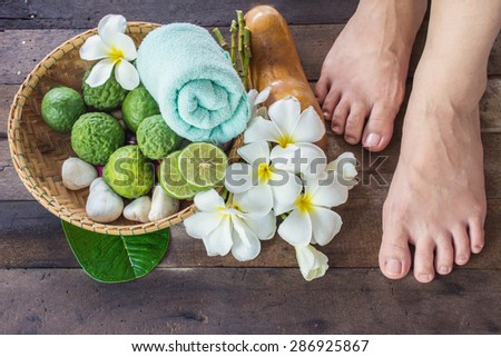 beautiful female feet with Kaffir Lime - wooden background - stock photo