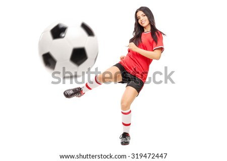 Beautiful female football player shooting a ball and looking at the camera isolated on white background - stock photo