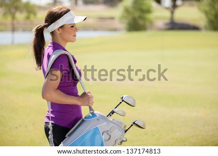 Beautiful female golfer carrying a golf bag and looking towards copy space - stock photo