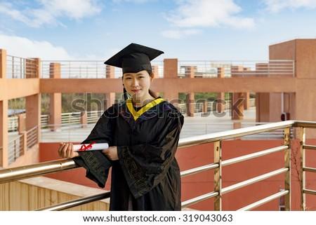 Beautiful female graduate wearing a graduation gown, - stock photo