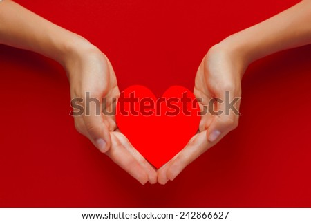 Beautiful female hand holding the red heart cut out of paper - stock photo