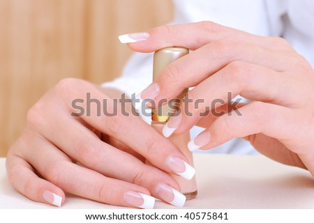 Beautiful female hands with beauty french manicure holding bottle enamel - stock photo