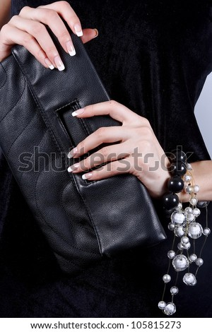 Beautiful female hands with manicure hold a black handbag - stock photo