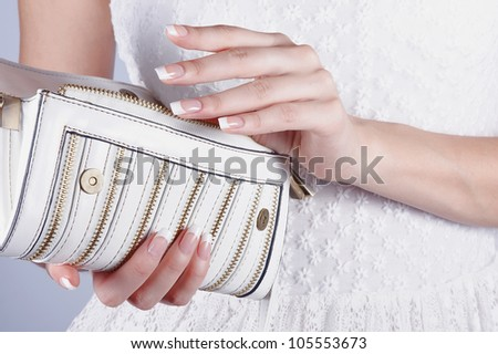 Beautiful female hands with manicure hold an open white handbag - stock photo