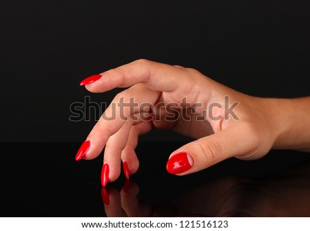 Beautiful female hands with red nails isolated on black - stock photo