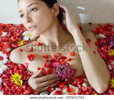 Beautiful female in bath with flower - stock photo