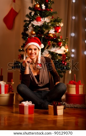 Beautiful female in Santa Hat near Christmas tree and present boxes - stock photo