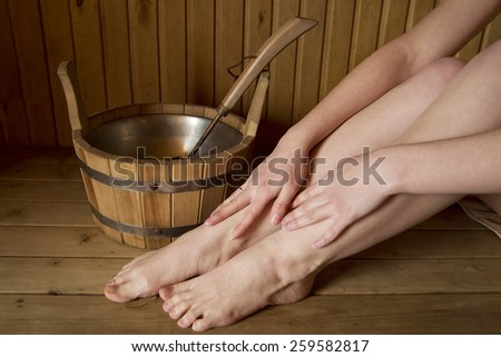 Beautiful female legs in sauna, bath accessories. Wooden bucket and sticks - stock photo