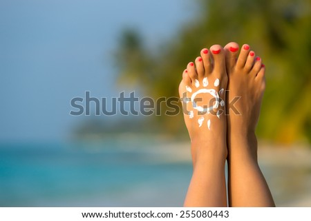 Beautiful female legs in the tropical beach conceptual image of vacation - stock photo