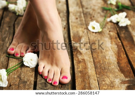 Beautiful female legs on rustic wooden floor background - stock photo