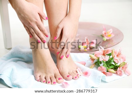 Beautiful female legs on  towel, on light  floor background - stock photo