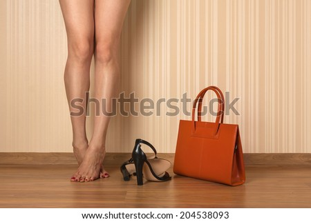 Beautiful female legs, shoes and bag, on wall background - stock photo