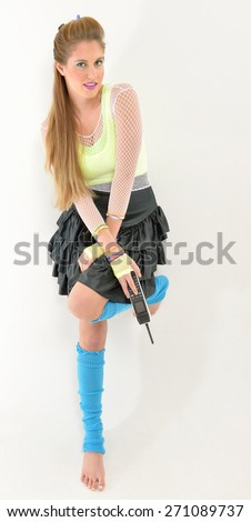 Beautiful female model from the 1980's - wearing fishnet top over neon tank tops, bright leg warmers, and black ruffled skirt. Also with neon bracelets and lace gloves and large old mobile phone,  - stock photo
