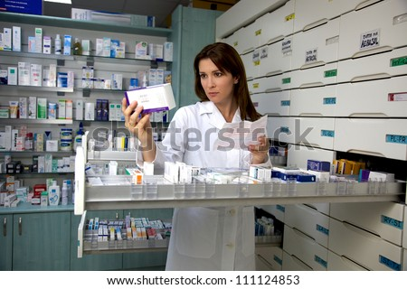 Beautiful female model pharmacist looking at medicine - stock photo