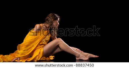 Beautiful female model with bright yellow dress, beautiful legs and perfect skin over black in studio - stock photo