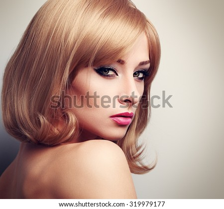 Beautiful female model with fashion blond hairstyle and green eyes looking sexy. Closeup toned portrait - stock photo