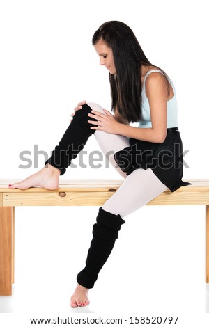Beautiful female modern jazz contemporary style dancer isolated on a white background. Dancer is wearing a blue leotard, black skirt and leg warmers and is holding her injured knee. - stock photo