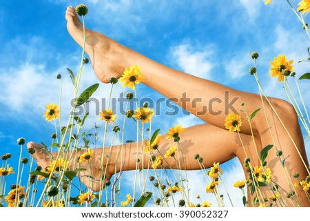 Beautiful female naked legs in field flowers against sky background - stock photo