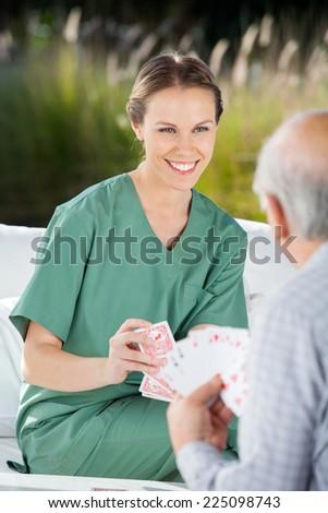 Beautiful female nurse playing cards with senior man at nursing home - stock photo