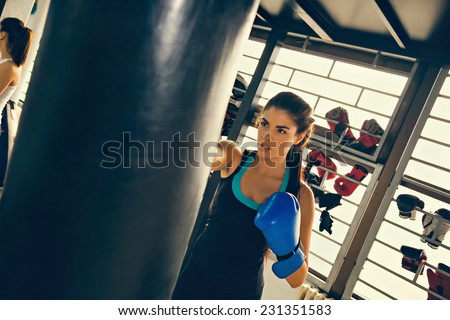 Beautiful Female Punching A Bag With Boxing Gloves On - stock photo