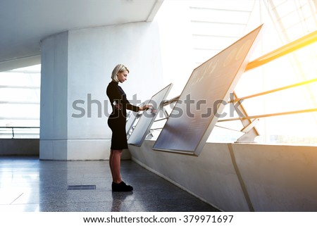 Beautiful female reading advertising about a project on interactive computer display while standing in office interior, businesswoman searching information on high tech modern device  - stock photo