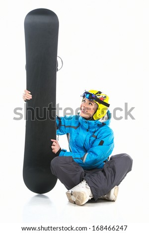 Beautiful female snowboarder sitting with snowboard in hands Looking at the snowboard isolated over white background  - stock photo