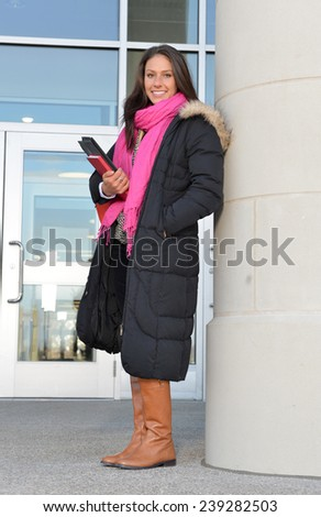 Beautiful female student (brunette) standing outside in late fall or winter studying - building entrance behind her - stock photo