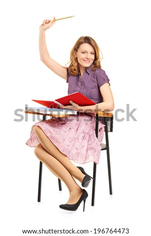 Beautiful female student with raised hand seated in a school desk isolated on white background - stock photo