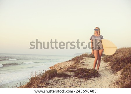 Beautiful female Surfer looking for the waves - stock photo