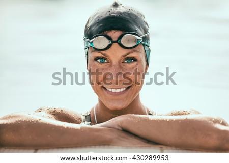 Beautiful Female Swimmer on pool edge - stock photo