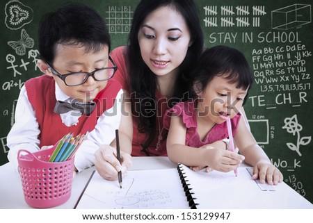 Beautiful female teacher help children write letters in class - stock photo