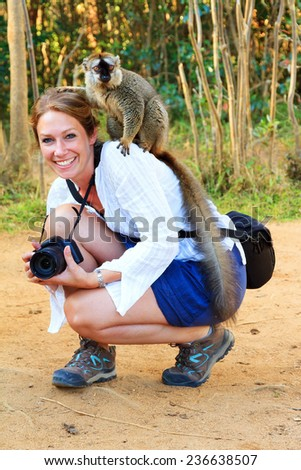 Beautiful female tourist having fun with a lemur on her shoulder in Madagascar - stock photo