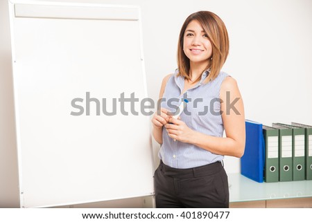 Beautiful female tutor standing next to a flip chart and about to teach a class - stock photo