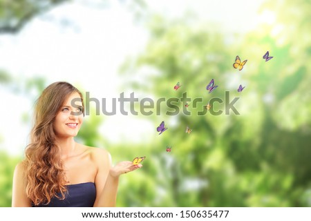 Beautiful female with a butterfly on her hand, posing in a park - stock photo