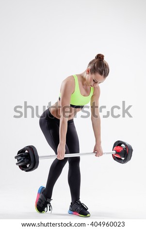 beautiful female with barbell posing on studio background - stock photo