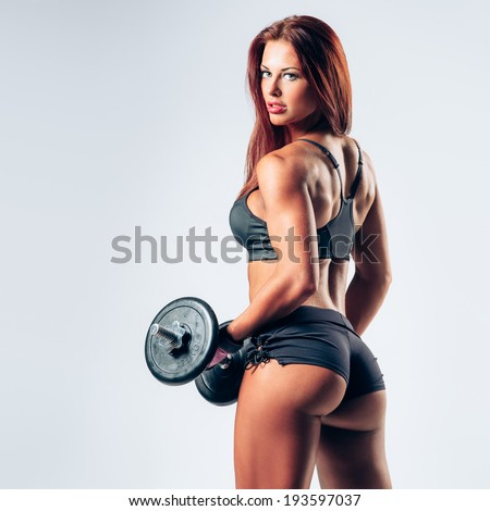 beautiful female with dumbbells posing on studio background - stock photo