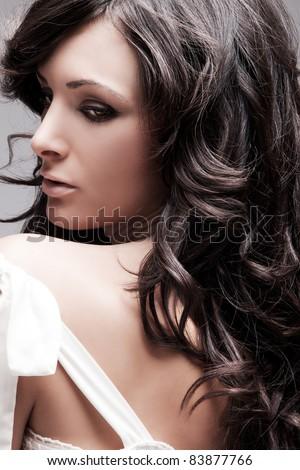 beautiful female with long wavy hair black hair, studio portrait - stock photo