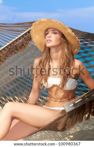 Beautiful female with straw hat sitting in hammock on sunny beach - stock photo