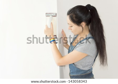 Beautiful female worker finishing concrete wall in a close up shot - stock photo