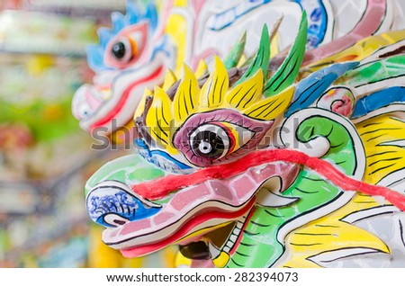Beautiful festive colourful dragon stone head in vietnamese buddha temple. It's painted in bright yellow, green, blue and green colors. - stock photo